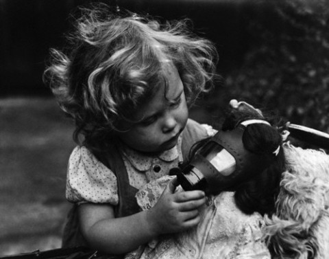 Girl Holds Doll and Gas Mask